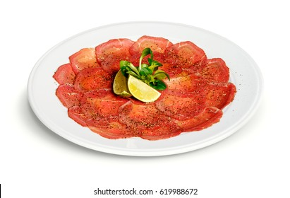 Smoked beef carpaccio with the lemon slices and the crushed pepper isolated on white