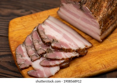 Smoked brisket sliced on a wooden chopping board. Close-up, selective focus.
