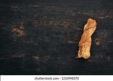 Smoked Cheese Suluguni. Top view. On a black wooden background. Free copy space.