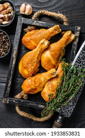 Smoked chicken leg drumsticks with herbs and spices. Black wooden background. Top view.