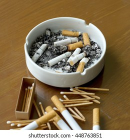 smoked cigarettes in white ashtray and matchstick on wooden table