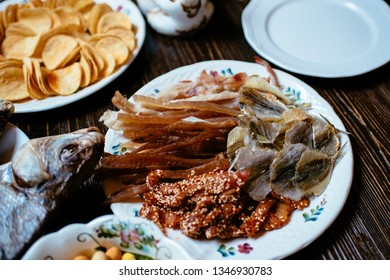smoked fish, chips, peanuts, snacks on white plates on a wooden table