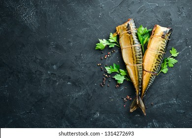 Smoked Fish Mackerel. On a black stone background. Top view. Free copy space.
