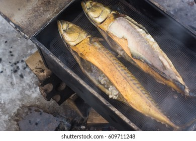 Smoked fish  in a metal smokehouse outside.