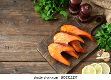 Smoked fish steaks trout on a serving board on a wooden kitchen table closeup