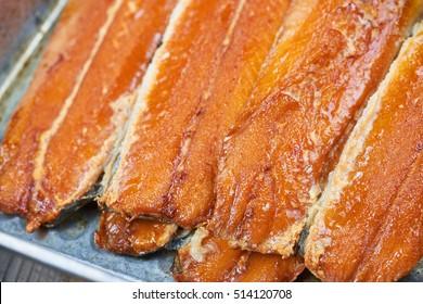 Smoked fish in a tin pan. Smoked herring