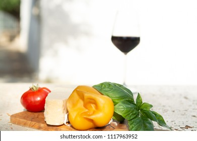 Smoked Fresh South Italian traditional cow or cow and sheep semi-soft cheese Scamorza, parmezan and red wine, served outdoor