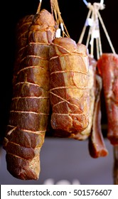 Smoked ham meat roasted sliced barbecue pork ribs in a traditional way hanging on dark background