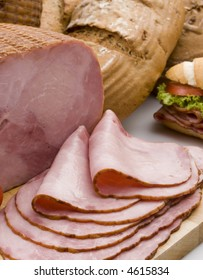 a smoked ham  piece and slices still life over a table