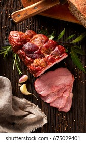 Smoked ham sliced on a wooden rustic table with addition of fresh aromatic herbs and spices, top view.  Natural product from organic farm, produced by traditional methods