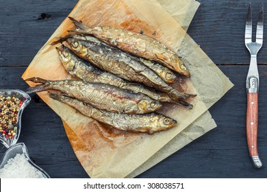 Smoked herring in the old paper on wooden background