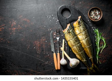 Smoked mackerel on a chopping Board with garlic, rosemary and spices. On dark rustic background