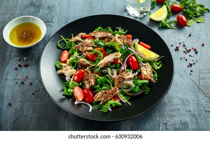 Smoked Mackerel Salad with tomato, chopped red onion, Ruccola on black plate.