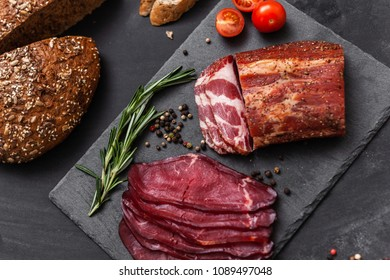 Smoked meat with ingredients on the black stone board, top view
