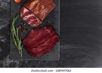 Smoked meat with ingredients on the black stone board, top view, place for text
