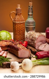 Smoked meat raw bacon and sausages with vegetables and salad with bottles of alchohol vodka and wine