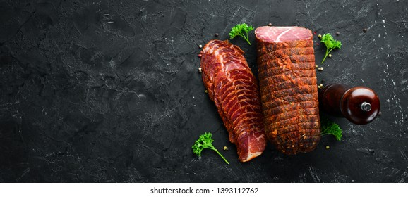 Smoked meat with spices and herbs. On a black wooden background. Top view. Free space for your text.