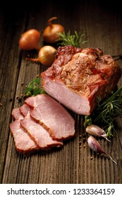 Smoked meats, sliced smoked pork loin on a wooden  table with addition of fresh  herbs and aromatic spices.