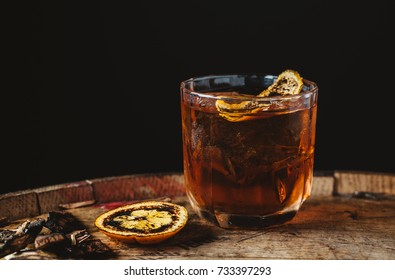 Smoked old fashioned cocktail garnished with an orange peel on dark wooden background