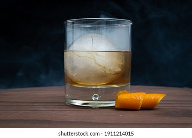 Smoked old fashioned with a spherical ice cube on a wooden table