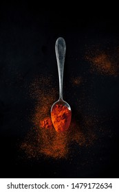 Smoked paprika, spicy, sweet on a teaspoon on a black background.