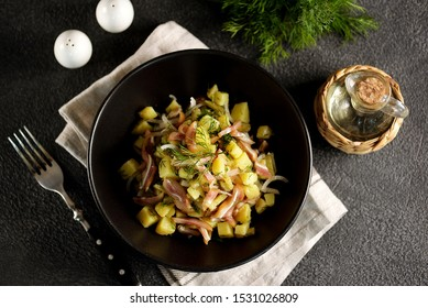 Smoked pork ears salad with boiled potatoes, pickles, onions, dill and olive oil.