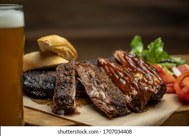 Smoked pork ribs with tomatoes, salad and bread on wood cutting board with glass of beer