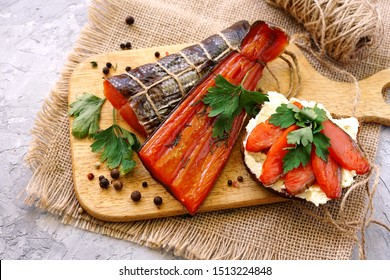 Smoked red fish with herbs and pepper. Spices for fish, food photography. Pink salmon on a cutting board on a gray background with craft paper. Slicing fish for a sandwich