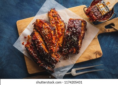Smoked Roasted pork ribs over blue background. Barbeque spicy ribs. Traditional american BBQ food.