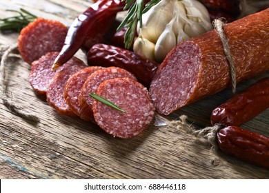 Smoked salami on a old wooden table. Sausages with rosemary , garlic and pepper.