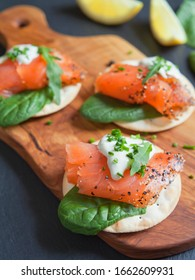 Smoked Salmon appetisers - delicious fish, black pepper, cream cheese, spinach,  green garnish.