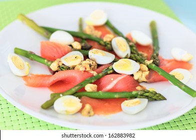 Smoked salmon with asparagus and quail eggs served in a dish with hazelnuts and mustard