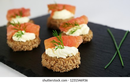 Smoked salmon canapes with cheese cream and dill on brown bread over black slate platter