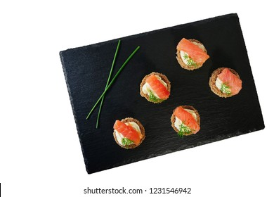 Smoked salmon canapes with cheese cream and dill served on black slate platter isolated on white background, top view, overhead.