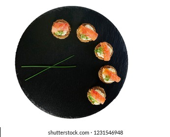 Smoked salmon canapes with cheese cream and dill served on round, black slate platter isolated on white background top view, overhead.
