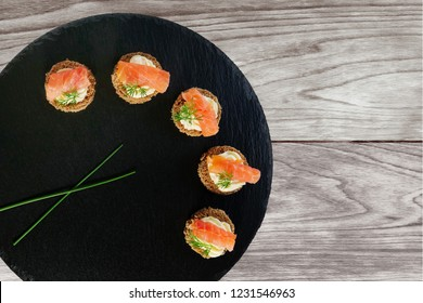 Smoked salmon canapes with cheese cream and dill served on round black slate platter over wooden background, top view, overhead