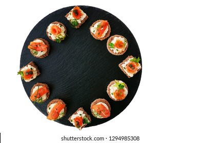 Smoked salmon canapes with cheese cream and dill served on black round slate platter isolated on white background, top view, overhead