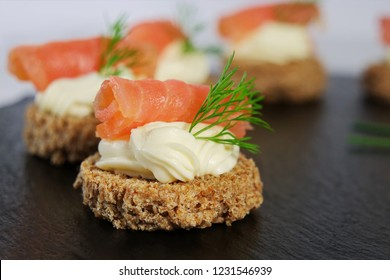 Smoked salmon canapes with cream cheese and dill on brown bread over black slate platter, shallow dof