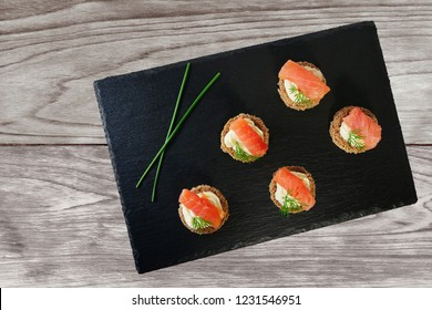 Smoked salmon canapes with cream cheese and dill served on black slate platter over wooden table, top view, overhead.