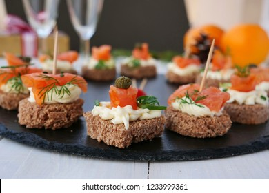 Smoked salmon canapes with cream cheese and capers on rye bread over black slate platter on a crowded party table, shallow dof
