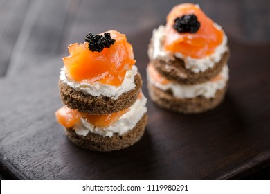 Smoked salmon with creamy cottage cheese and black caviar. Cater