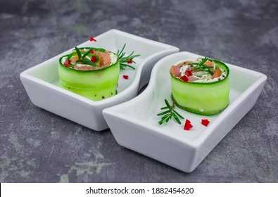 smoked salmon with cucumber and  soft cheese rolls on white plat