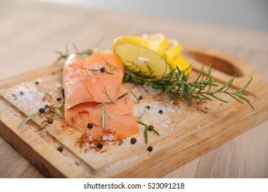 Smoked salmon fillet with rosemary, pepper and salt on the desk.