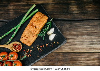 Smoked salmon fillet with rosemary, seasonings, garlic, cherry tomatoes and asparagus on a black stand, wooden background. Top view, copy space