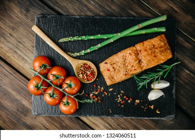 Smoked salmon fillet with rosemary, seasonings, garlic, cherry tomatoes and asparagus on a black stand, wooden background.