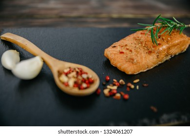 Smoked salmon fillet with rosemary, seasonings, garlic, on a black stand, wooden background.