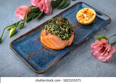 Smoked salmon fillet stuffed with cheese, avocado and spinach. Natural delicious food. Greek cuisine menu. Still life in a marine style on a blue background.