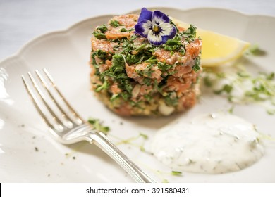 Smoked Salmon, Parsley and Quinoa Cake with a Lemon and Dill Sauce, with a Lemon Wedge on a White Plate