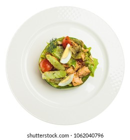 Smoked salmon salad isolated on white background. Salmon, eggs, lettuce and tomatoes on white plate, top view