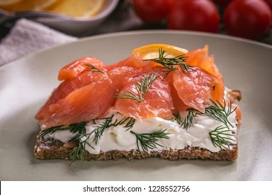 Smoked salmon sandwich with cream cheese on plate closeup
